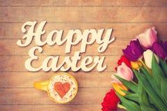 Capuchino y palabras Pascua feliz cerca de las flores Imagen de archivo libre de regalías