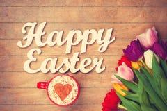 Capuchino y palabras Pascua feliz cerca de las flores Imagenes de archivo