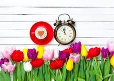 Capuchino y reloj cerca de las flores Imágenes de archivo libres de regalías