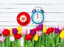 Capuchino y reloj cerca de las flores Imagenes de archivo