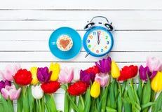 Capuchino y reloj cerca de las flores Fotos de archivo