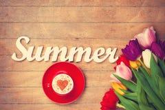 Capuchino y verano de la palabra cerca de las flores Foto de archivo libre de regalías