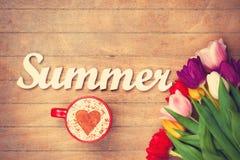 Capuchino y verano de la palabra cerca de las flores Foto de archivo