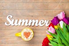 Capuchino y verano de la palabra cerca de las flores Imagenes de archivo