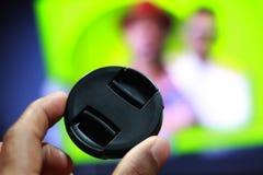 Capuchon d'objectif de caméra avec la main et le fond coloré photographie stock libre de droits