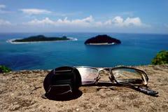 Capuchon d'objectif, verres, îles, et océan image stock