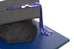 Capuchon et diplôme de graduation d'isolement Photographie stock