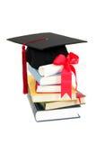Capuchon et diplôme de graduation sur la pile de livres Photographie stock libre de droits