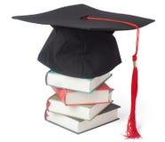 Capuchon et livres de graduation Photographie stock