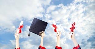 Capuchons de graduation projet?s dans le ciel image stock
