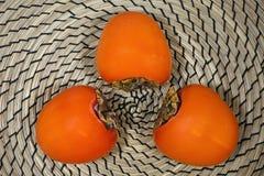 Caqui fetal tres en un fondo de mimbre marrón claro Fotografía de archivo