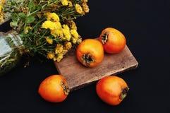 Caqui maduro fresco em um fundo preto Fruto dos caquis, caquis doces maduros Imagens de Stock
