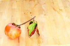 Caqui orgânico natural com folhas amarrotadas em um backgro de madeira Imagem de Stock