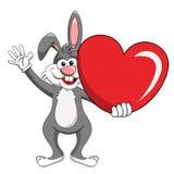 Carácter de la historieta o conejo divertido de la mascota que sostiene isola grande del corazón Imagen de archivo libre de regalías