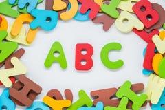 Carácter de madera colorido con el fondo blanco y palabra de ABC en el centro Imagenes de archivo