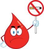 Carácter rojo enojado de la mascota de la historieta de la gota de sangre que soporta una muestra de no fumadores Foto de archivo