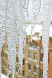 Carámbanos brillantes que están colgando abajo de un tejado Viejo paisaje urbano de la ciudad Textura del hielo Foto de archivo
