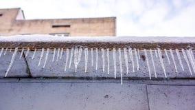 Carámbanos de la ejecución del invierno en el tejado de la casa Cerca de carámbanos como textura del invierno Foto de archivo libre de regalías