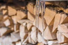 Carámbanos delante de la leña partida en invierno imágenes de archivo libres de regalías