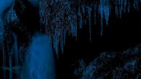 Carámbanos en la noche contra la oscuridad del bosque y del crepúsculo del invierno imagen de archivo