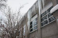 Carámbanos enormes en el tejado del edificio Riesgo mortal, peligro a los seres humanos imagen de archivo