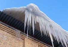 Carámbanos grandes que cuelgan en el tejado de la casa Imagen de archivo