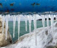Carámbanos que cuelgan de la barra de metal, el lago Michigan en fondo imagen de archivo libre de regalías