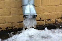 Carámbanos que se congelan abajo de un tubo del agua en el tejado Fotos de archivo libres de regalías