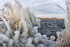 Carámbanos y esculturas de hielo en la orilla de un lago durante un encanto frío en invierno foto de archivo libre de regalías