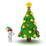 caráter 3D com o chapéu do duende que mostra uma árvore de Natal decorada Foto de Stock Royalty Free