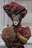 Caráter do carnaval de Veneza vestido em um traje colorido vermelhos e do ouro e em uma máscara em fevereiro Veneza Itália de Ven fotos de stock royalty free