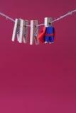 Caráter poderoso do super-herói no cabo azul do vermelho do terno foto do conceito do líder e da equipe do pregador de roupa hang Fotografia de Stock