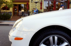 Car. The side of a car with a cafe in the background Royalty Free Stock Images