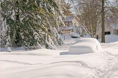 Car abandoned after snowstorm. A car completely covered in snow and abandoned on a residential street after a heavy winter snowstorm Royalty Free Stock Images