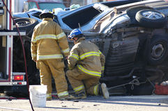 Car Accident. With firemen investigating the scene Royalty Free Stock Photos