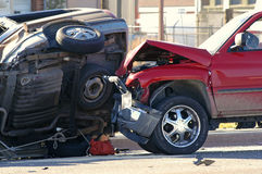 Car Accident. With closeup of smashed car hood and car on its side Royalty Free Stock Photography
