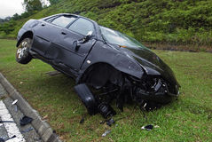 Car accident. A damaged black car after an accident at a roadside Stock Images