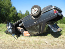 Car accident. Damaged car after the traffic accident, turned overhead, driver inside Stock Photo