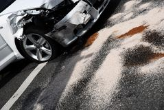 Car Accident Aftermath. A white car after and accident with absorbent material on the street soaking up the cars fluids stock photo