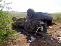 Car accident. Broken turned over car lies near road Royalty Free Stock Photo
