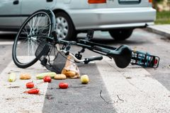 Car accident concept. Bicycle, broken glasses and groceries lying on the pedestrian crossing stock images