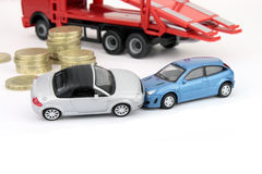 Car Accident. A car crash involving two cars, with coins and a breakdown truck against white in the background Royalty Free Stock Images