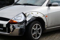 Car accident damage. Front left fender damage to a silver vehicle that has been in an accident Stock Image