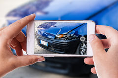 Car accident phone photography. A woman using a smart phone to take a photo of the damage to her car caused by a car crash royalty free stock photos