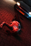 Car Accident and Police Lights. A supposedly dead or injured woman laying on the ground after she has been hit by a car in an accident at night Stock Image