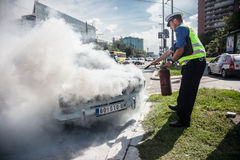 Car accident. The policeman douses a fire after car ignition accident  at one of crossroads of Belgrad. Serbia Royalty Free Stock Images