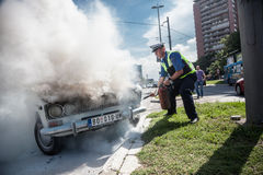 Car accident. The policeman douses a fire after car ignition accident  at one of crossroads of Belgrad. Serbia Royalty Free Stock Image