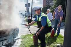 Car accident. The policeman douses a fire after car ignition accident  at one of crossroads of Belgrad. Serbia Stock Image