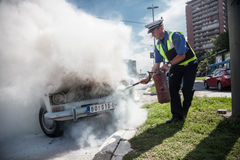Car accident. The policeman douses a fire after car ignition accident  at one of crossroads of Belgrad. Serbia Stock Images
