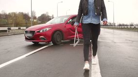 Car accident on the road, the girl puts a warning sign near the car. A young girl in jeans and a leather jacket sets an emergency stop sign near her wrecked car stock footage